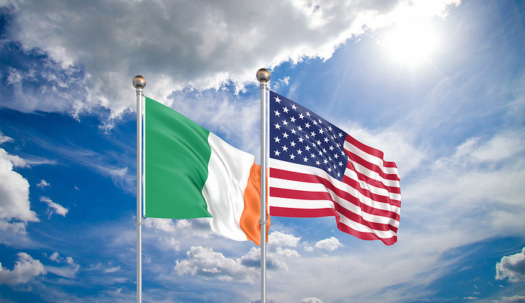 Ireland and US Flags Against Bright Sky