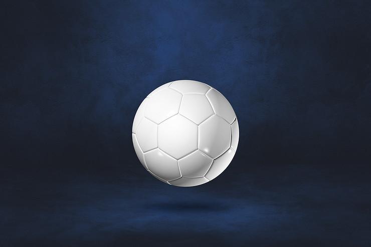 White Football Isolated Against Dark Blue Background