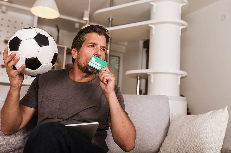 Man kissing his credit card holding a football